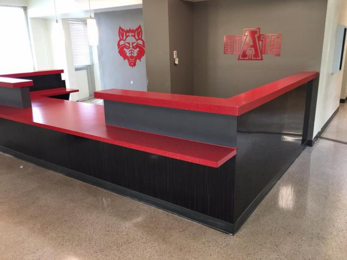 This is a reception desk at Kays hall at Arkansas State University. It was resurfaced with a Scarlett red with a Stonewall gray Multi-Stone.]